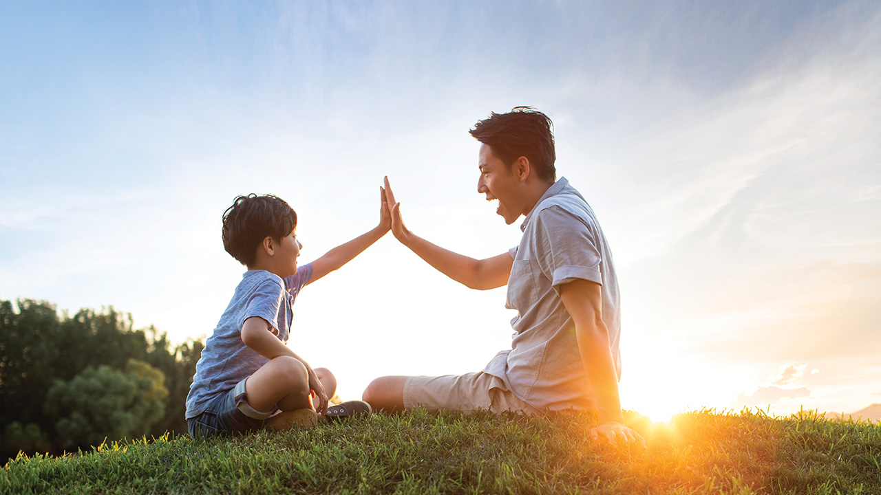 A father and son giving each other a high five on meadow; image used for HSBC Singapore Emerald Life Legacy Plan.
