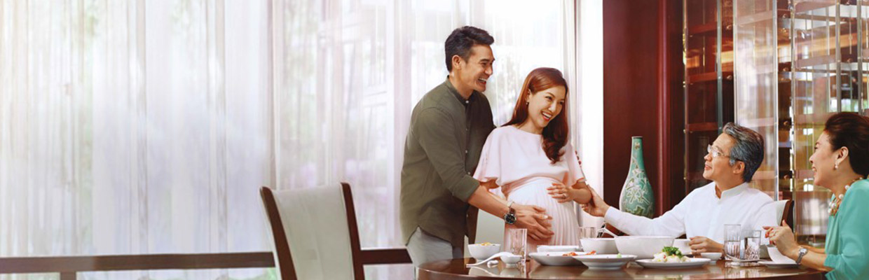 Pregnant woman has lunch with her husband and family, image used for HSBC Jade Legacy Universal Life Plans.